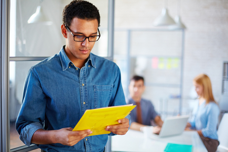 office environment: Young businessman reading paper in working environment