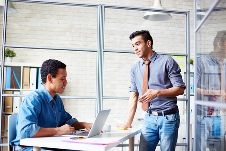 office environment: Two young businessmen communicating in office