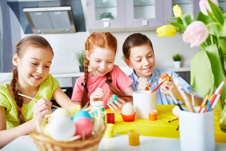 children painting: Children enthusiastic about painting eggs