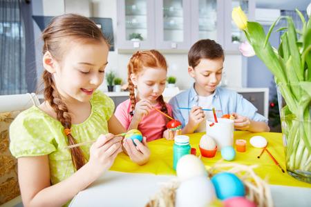 children painting: Children painting eggs with gouache Stock Photo