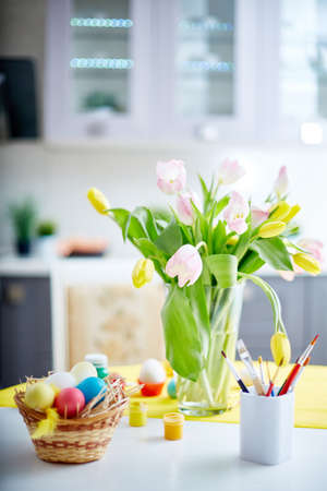 tulips in vase: Vase with tulips and colored eggs Stock Photo