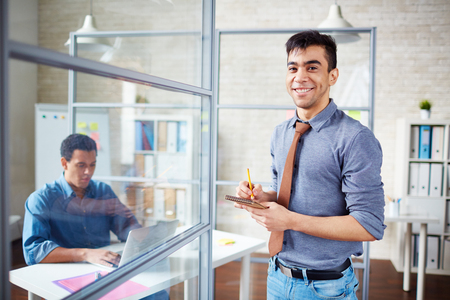 look latino: Businessman with notepad looking at camera in office Stock Photo