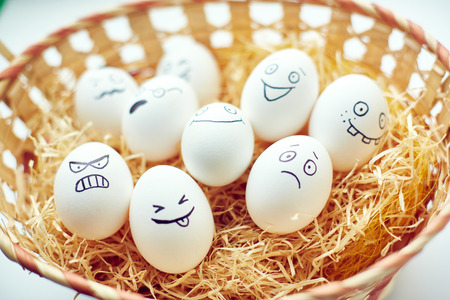 emotions: Basket with funny eggs with painted faces expressing different emotions
