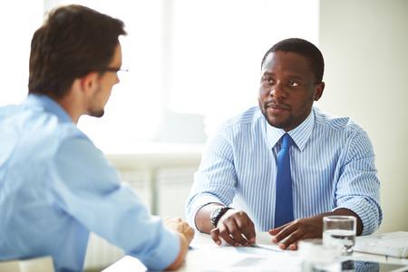 personas hablando: Encargado serio que habla con un candidato