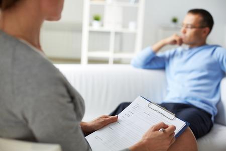 女性の心理学者は彼女の患者のカードに記入 写真素材