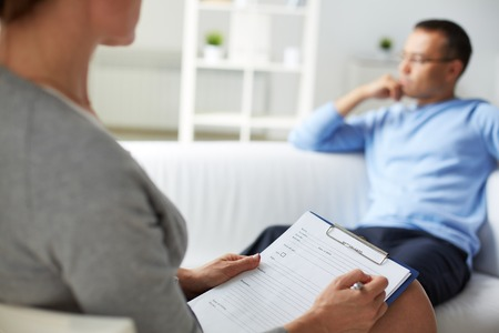 patient notes: Woman psychologist filling in card of her patient