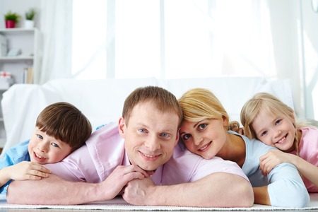 Portrait of family posing together on floor photo