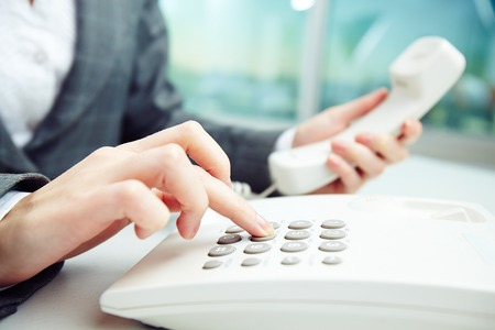 telephony: Close-up of female hand dialing number