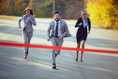 Businessman competing with two businesswomen Archivio Fotografico