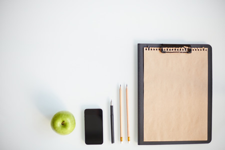 Writing instruments, smartphone, clipboard and apple photo