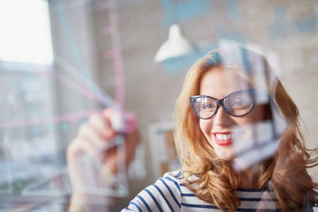 success strategy: Young woman drawing on glass