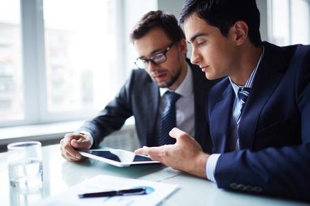 ejecutivo en oficina: Dos hombres de negocios que trabajan con el touchpad en el encuentro en oficina Foto de archivo