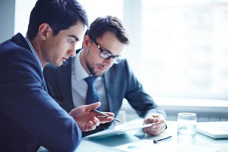 reunion de trabajo: Hombre de negocios serio que explica los datos a su colega en la reuni�n
