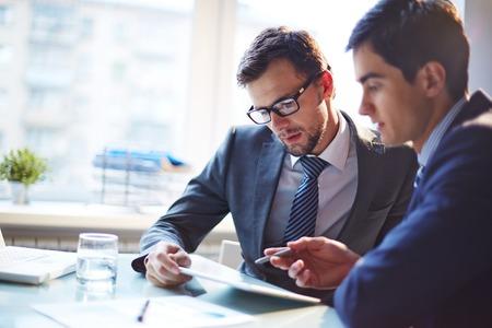 hombre de negocios: Hombre de negocios serio escuchando sus explicaciones colega en reuni�n Foto de archivo