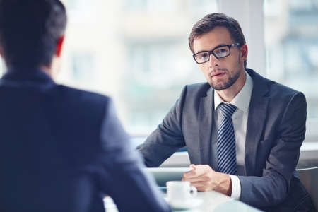 serious businessman: Serious businessman looking at camera at workplace with his colleague near by Stock Photo