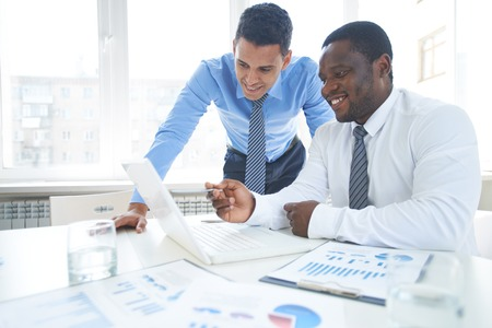 discussing: Two businessman discussing ideas on laptop Stock Photo