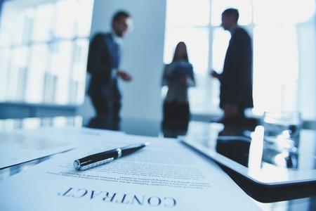 legal document: Primer plano de contrato con la gente de negocios en el fondo