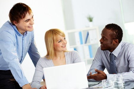 Three colleagues communicating in office