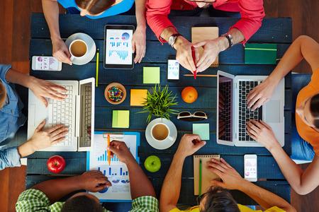 mujeres trabajando: Vista de �ngulo alto de personas que trabajan juntas en una misma mesa Foto de archivo