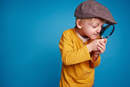 Inquisitive boy with magnifying glass 版權商用圖片 - 38150401