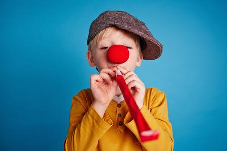 Kleiner Junge bläst eine Partei Horn Gebläse