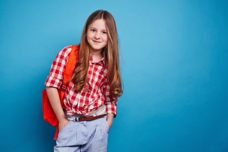 schoolbag: Smiling girl with schoolbag looking at camera Stock Photo