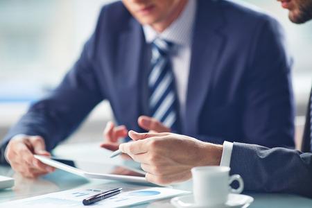 reuniones empresariales: Las manos de los hombres de negocios que trabajan con el touchpad Foto de archivo