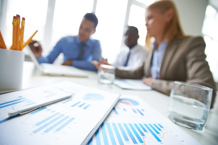 papeles oficina: Primer plano de los informes financieros con portapapeles en la mesa