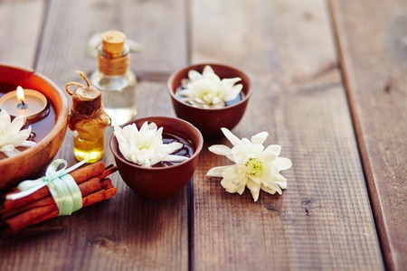 Bowls with flowers, bunch of cinnamon for aromatic oil