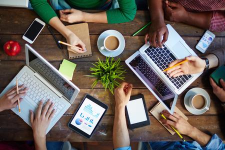 Alto, ângulo de mesa e pessoas sentadas no que faz com laptops e touchpads Imagens