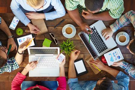 Erhöhte Ansicht von Menschen kommunizieren die am Tisch mit ihren Geräten