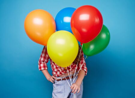 Little girl hiding behind bunch of colorful balloons photo
