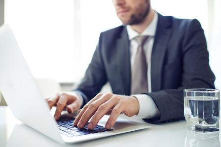 エレガントな男のノート パソコンでの作業