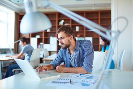 ležérní: Mladý muž pomocí přenosného počítače v kanceláři