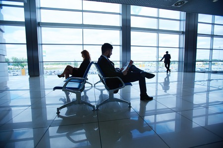 corporate travel: Group of businesspeople waiting for their departure in airport Stock Photo
