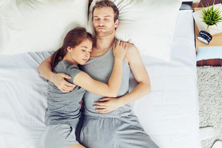 抱擁で寝ている若いカップル