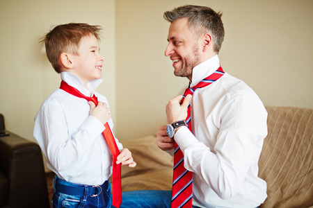 Father and son knotting ties