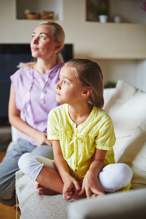 sideway: Two members of family looking at sideway and sitting on sofa