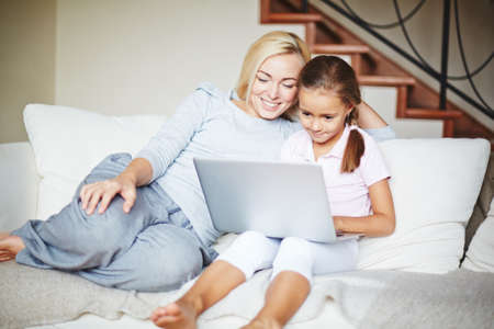family sofa: Smiling mother and daughter using laptop at home