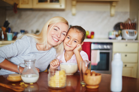 beautiful: Happy mother and daughter sitting at table and looking at camera