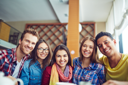 Five friendly young people looking at camera Stock Photo