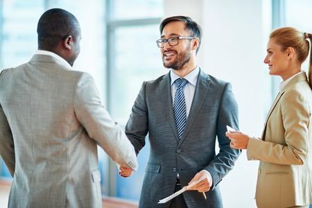 handshaking: Happy businessmen handshaking after striking deal Stock Photo