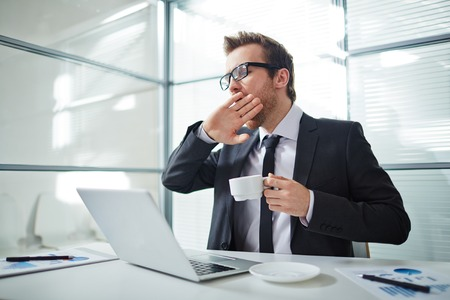 tired businessman: Tired man with cup of coffee yawning at workplace in office