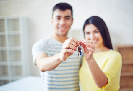 settler: Young couple holding key from new flat