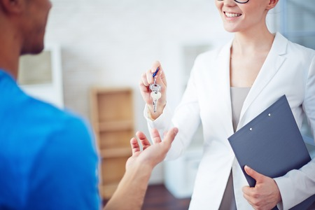 brokers: Smiling woman giving buyer key from new residence Stock Photo
