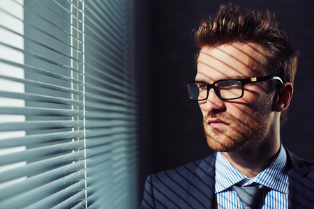 venetian blind: Confident young businessman in eyeglasses looking through venetian blinds