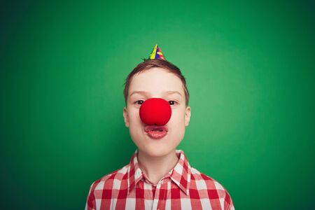 clown nose: Funny boy with red clown nose looking at camera at fool�s day celebration
