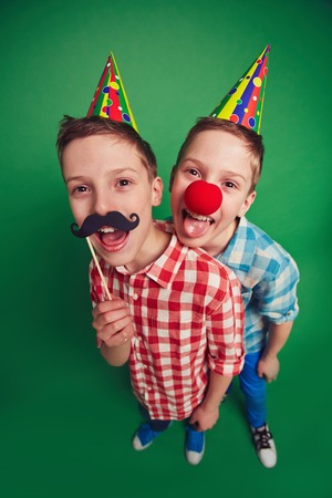 clown nose: Hilarious twins with clown nose and moustache during fool�s day celebration