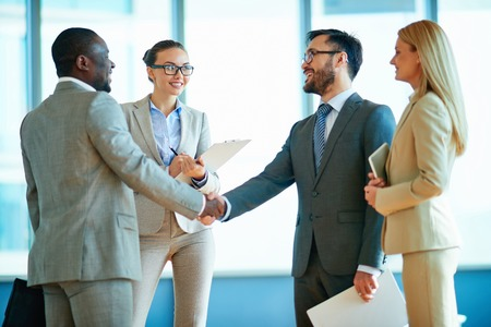 Happy businessmen handshaking with their two colleagues near by