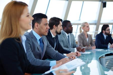 curso de capacitacion: Fila de los hombres de negocios serios que asisten a seminario Foto de archivo